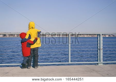 children stand in an embrace on the waterfront. two kids hugging looking at the sea. empty space for your text