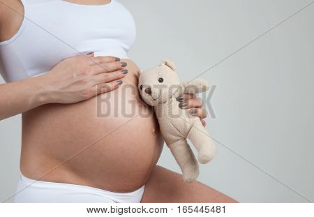 Little bear listen for belly of a pregnant woman isolated on white background