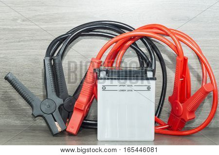 A motorcycle battery and battery booster cables