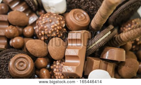 Chocolate, candies, and cookies on table close-up