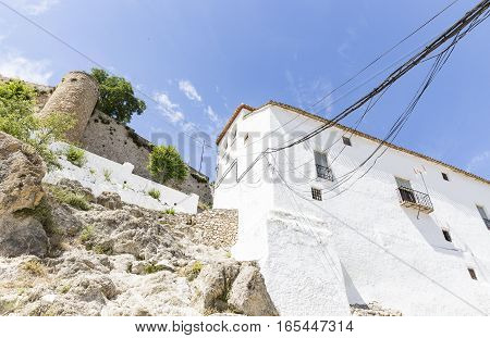 a white building with electric cables and the ancient castle of Moclin, Granada, Spain