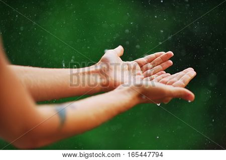 hand catching rain drops on blurred background