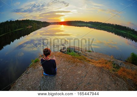 Young woman sitting on the stone enjoying peaceful moment of sunset. In the reflection of the lake water sees clouds and sun.