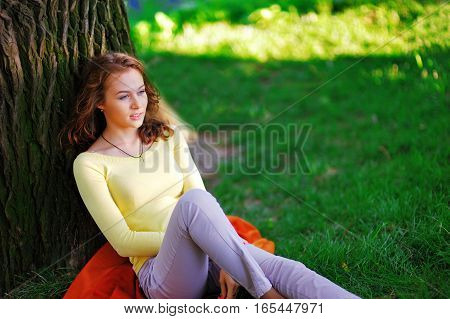 young girl sitting in the shade of a tree and enjoy the beauty of nature