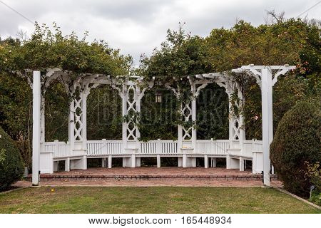 Los Angeles, CA, USA - January 15, 2017: White porch gazebo with lights in a rose garden at the Los Angeles Arboretum in Southern California. Editorial use.