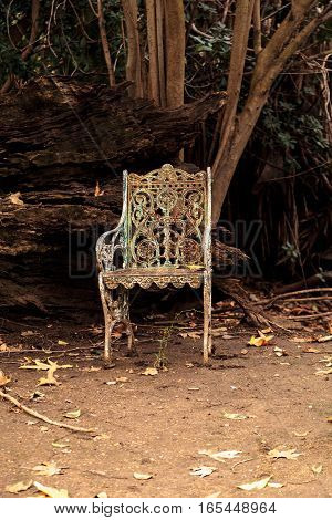 Rusty old white Victorian iron lawn chair in a spooky winter garden