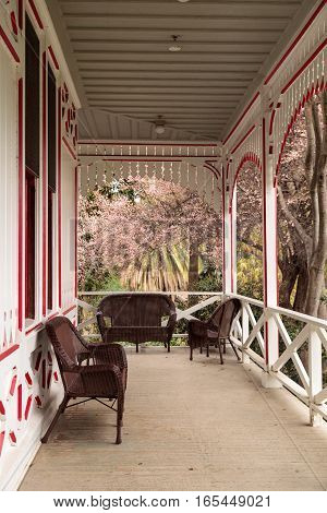 Los Angeles, CA, USA - January 15, 2017: Red and white porch of a Victoria cottage with pink flowers in bloom on a tree at the Los Angeles Arboretum in Southern California. Editorial use.