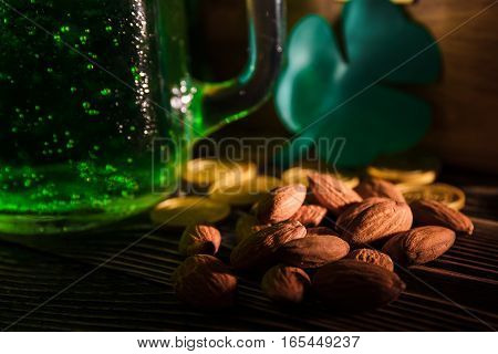 St Patrick's day nuts and green beer on a dark background
