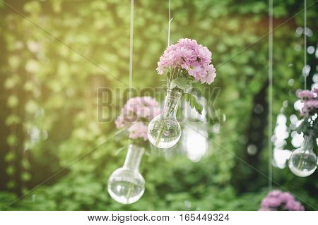 Wedding floral decoration in the form of glass-vases and bouquets of flowers hanging from the ceiling