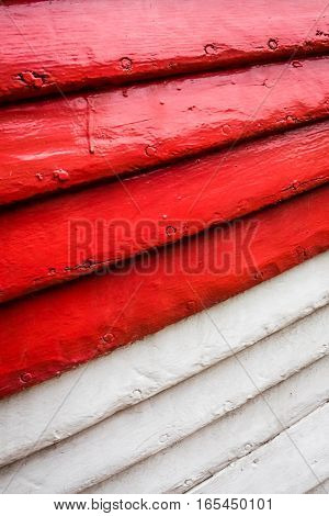 Red and white rows of painted wooden side of a fishermen boat