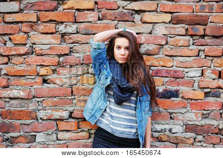 Young pretty girl with long brown hair dressed in a denim jacket pants and black scarf standing near a brick wall