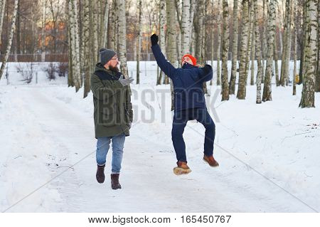 Two friends go on a winter birch forest and talking. One of them slipped and lost his balance waved his hands trying to stay on his feet.