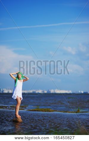 Portrait of a young slender girl standing on a rock in the water near shore on background of blue cloudy sky and deep blue Bay with blurred outline of city buildings on other side.