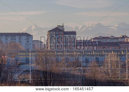 Italy Turin - January 5 2015: view of Buildings and white mountains on background. Lingotto district on January 05 2015 in Turin Italy.