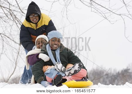 Brothers and sister sliding on a sled.