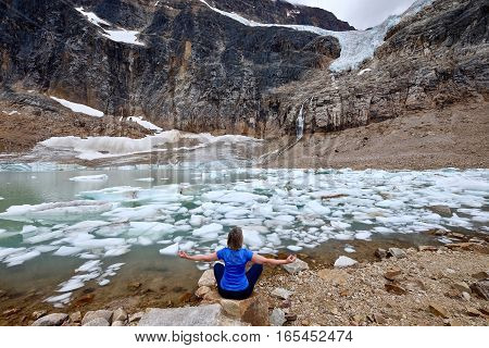 Woman in yoga pose at a moraine lake under  Angel Glacier at Mount Edith Cavell. Jasper National Park. Canadian Rockies. Alberta. Canada.