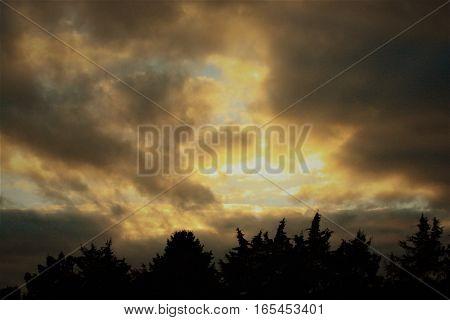 Sunshine peeking through the clouds at sunset.