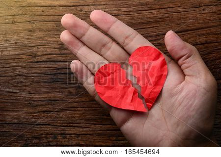 man holding a paper broken heart on wooden background
