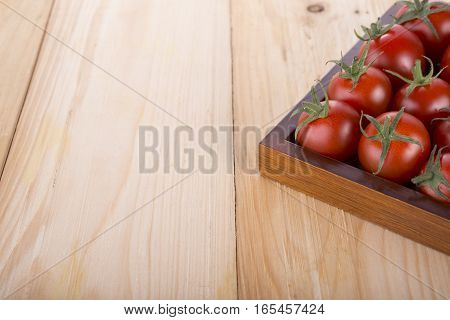 red tomato with stem in wooden box with left space for writing or text