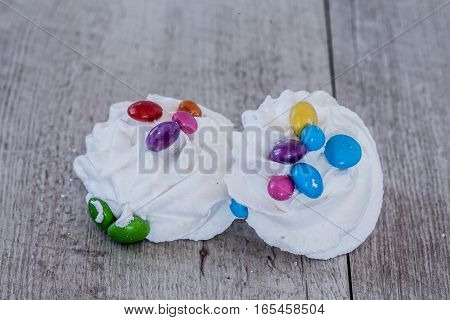 White meringue decorated with colorful candy on wood background.
