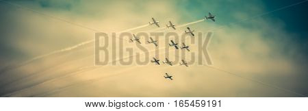 Airplanes flying high in formation during airshow on dramatic sky.