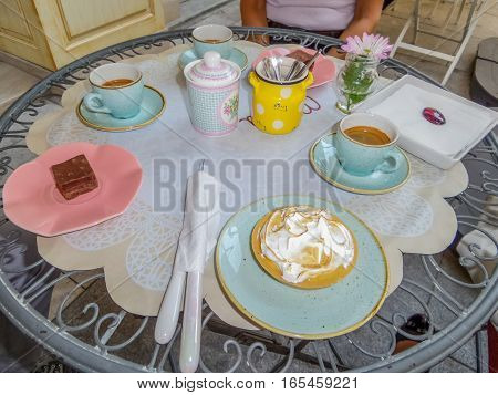 Table in coffee shop with hot coffee and pastry served in pastel colored pottery.