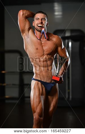 Male Fitness Competitor Showing His Winning Medal