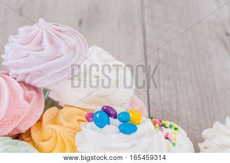 Mix o various flavours meringues on grey background with copy space.