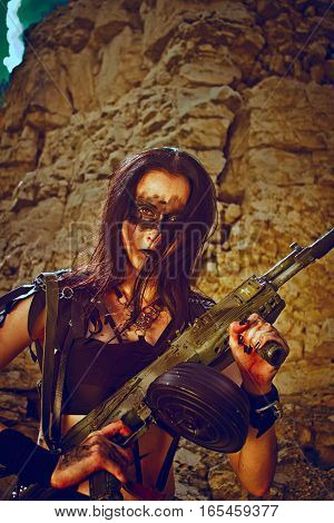Pretty post-apocalyptic warrior posing over rocks with automatic rifle