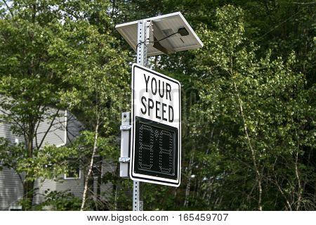 A solar powered speed radar by a suburban road.