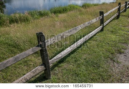 Sections of an old weathered wooden split rail fence.