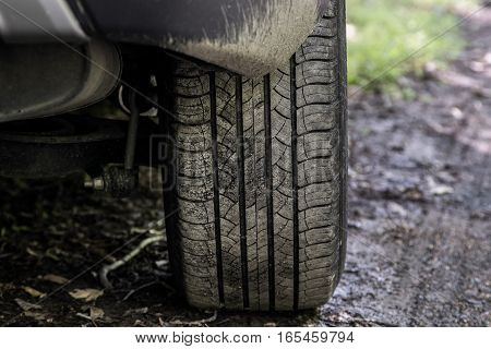A closeup view of a car tire on an unpaved road.