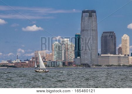 New York August 17 2016: A harbor view of Jersey City with a small sailboat in the foreground.