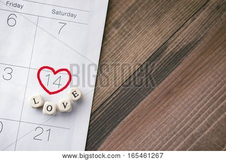 Valentine Day with word love on the calendar with wooden background
