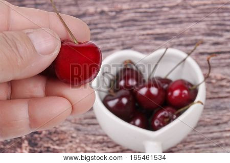 Hand-picked Cherriy And Cherries In Heart-shaped Mug On Wooden.