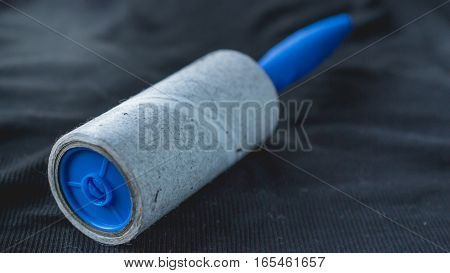 dirty roller for cleaning clothes on black shirt