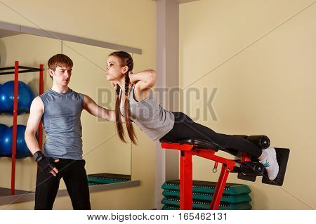 Personal trainer helps a girl to do exercises for the back. Healthy lifestyle concept. Fitness.