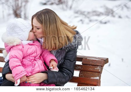 Mother keeps daughter in her arms and kisses her on the cold outdoors. She sat on the bench. Family walk in a winter park. Family happiness.