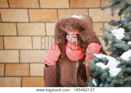 Pretty teen girl in pink knitted gloves hats and scarves fur hooded jacket winter walks in the park. She is laughing. Outdoor Activities. Youth fashion. Close-up portrait
