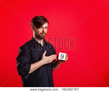Man holding a cube with the number nine. Numerals. A man shows a cube with the number nine