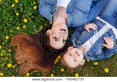 Mother and daughter lying on a green lawn among yellow dandelions. Girls dressed in denim jackets. Spring mood. Family look. Family time