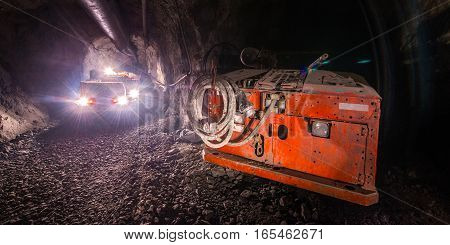 Gold mining underground. Loaded truck driving in the tunnel.