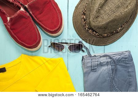 Outfit of men. Casual outfit with hatred shoesunglass and yellow t-shirt on blue wooden background.