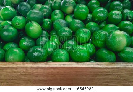 Stack of Limes on Fruit Shelf Stand with Wood for Copy Space at bottom