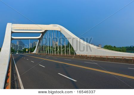 road through the bridge with blue sky background of a city.