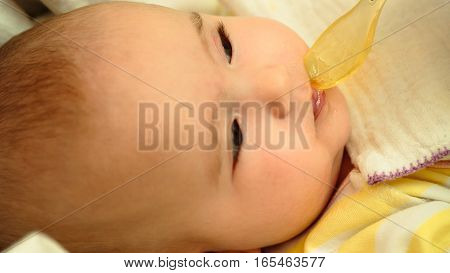 Mother feeds her little child baby puree with spoon close-up