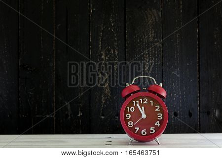 Alarm clock on white wood table five minutes to twelve o'clock