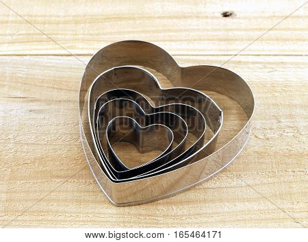 heart shaped cookie cutter on wooden kitchen table, tools for preparation Valentine snack