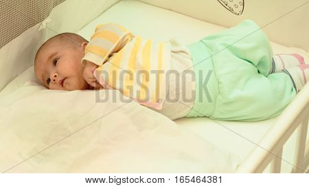 Little baby is resting in his crib close-up