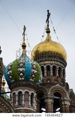 Close up of the onion domes on the Russian Orthodox church, the Church of Our Savior on Spilled Blood in St. Petersburg, Russia. The domes are gold, blue and green and topped with crosses.